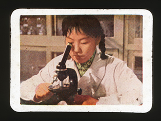 Slide depicting a female scientist looking into a microscope
