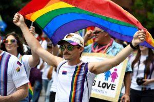 Man at JHU pride parade holding rainbow flag above his head