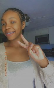 Picture of J'Naya Harris smiling and holding up two fingers in a peace sign. Image courtesy of J'Naya Harris